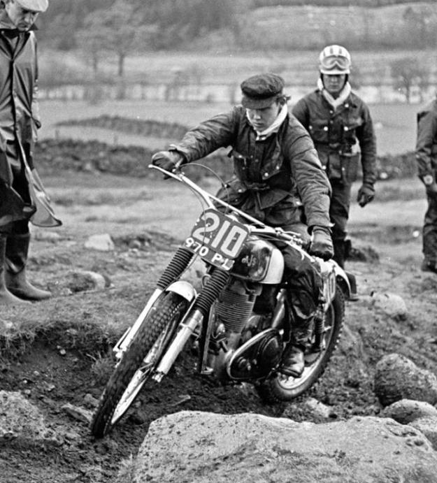 Rob on his 350 AJS at Achintee Farm, Ben Nevis, in the 1964 Scottish. The AJS supplied by Comerfords, hence the Surrey registration number 970PL. If you look closely the front wheel spindle nut has the ISDT type tommy-bar, obviating the need for a spanner. It also has the works style prop-stand tied to the front downtube by rubber bands and a small spigot mounted on the lower-most engine bolt and the attachment spigot mounting on the magneto mounting plate. Photo supplied by Rob Edwards. Photo copyright: Brian Holder.
